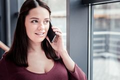Dark-haired cute woman feeling fascinated while talking by phone stock photo