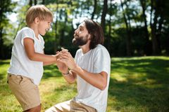 Dark-haired dad and his son dressed in white t-shirts fool around and having fun on the green lawn in the park on a stock photos