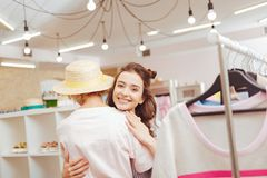 Dark-haired daughter joining her mother in shopping mall. Joining mother. Dark-haired daughter smiling broadly while joining her mother in shopping mall Royalty Free Stock Images