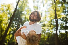 Dark-haired father with beard dressed in the white t-shirt is holding in the arms his blond son and smiling on a summer royalty free stock images