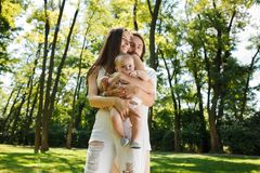 Dark-haired father of his beautiful wife holding in her arms a small charming daughter in a white dress in a park on a royalty free stock image