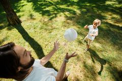 Dark-haired father and his little son dressed in the white t-shirts are playing football on a lawn on a warm day. stock photography