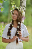Dark-haired girl with braids and daisies Stock Images