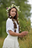Dark-haired girl with braids and daisies Royalty Free Stock Image