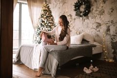 Dark-haired girl dressed in white sweater and pants holds a New Year gift in her hands sitting on the bed with gray stock photos