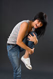 The dark-haired girl in jeans presses the left foo Royalty Free Stock Photos
