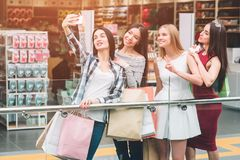 Dark-haired girl in pants is taking picture of herself with company. They are in mall. Girls are posing and having some. Fun Stock Photos