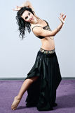 Dark-haired girl performing a belly dance Stock Photo