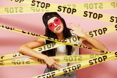 Dark-haired girl in pink sunglasses and cap looking out from behind yellow scotch tapes with inscriptions of word `stop stock images