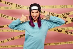 Dark-haired girl with purple hair tips dressed in blue sweatshirt and black hat shows rock sign on the background of stock images
