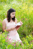Dark-haired girl reading a book on nature Royalty Free Stock Photo