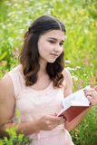 Dark-haired girl reading a book on nature Stock Photo
