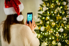 Dark-haired girl in Santa`s cap photographs the Christmas tree on mobile phone. Stock Images