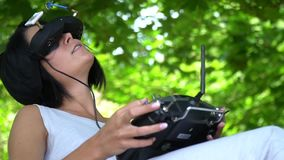 The dark-haired girl sits at the nature and emotionally controls the racing drone through virtual reality glasses