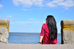 The dark-haired girl sitting on the beach. Girl sitting under a blue sky on the beach, rear view Royalty Free Stock Image