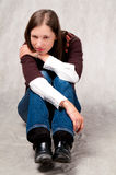 Dark haired girl sitting with legs straight. Dark haired girl sitting thinking with legs straigt and hands crossed in front thinking wearing blue jeans sweater stock image