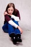 Dark haired girl sitting thinking on white Royalty Free Stock Image