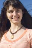 Dark-haired girl smiles Stock Images