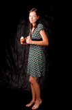 Dark haired girl standing colored dress on black Royalty Free Stock Photo