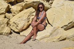 The dark-haired girl in a swimsuit on the yellow rocks Stock Images