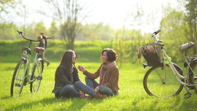 Dark-haired Girls are Enjoying Picnic Sitting on Green Grass Near the Bicycle and Trees in the Park. Young Female. Friends Have a Conversation Outdoors, HD stock footage