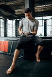 Dark-haired guy dressed in the grey t-shirt and black shorts sits on the border of boxing ring and wraps a hand bandage royalty free stock photos