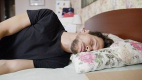Dark haired guy falls on bed with comfy pillow and immediately gets asleep. Mature bearded dark haired guy with mustache, wearing black t-shirt falls on bed stock video footage