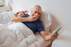 Dark-haired husband after seeing disturbing message from son. Disturbing message. Dark-haired husband feeling worried after seeing disturbing message from son royalty free stock photos