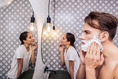 Dark-haired husband shaving his face standing near appealing wife. Near appealing wife. Dark-haired husband shaving his face standing near appealing wife wearing stock image
