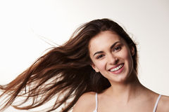 Dark haired, late teen girl, hair blowing, smiles to camera Stock Photo