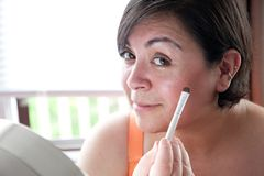 Beautiful curvy woman with makeup. A dark haired latina woman smiles at you as she applies her makeup by a mirror royalty free stock photo