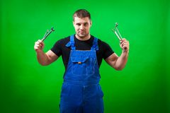 Dark-haired male construction. A dark-haired male construction worker in a black T-shirt and blue construction overall holds in his hands a new tool Stock Image