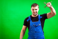 Dark-haired male construction. A dark-haired man construction  builder in a black T-shirt and blue construction overall holds in his hand a two new tool Stock Images