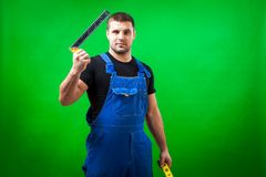 Dark-haired male construction. A dark-haired male construction worker in a black T-shirt and blue construction overall holds construction r L shape angle square Stock Photos