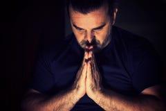 Man praying in dark. Dark haired man bowing his head in prayer Stock Images