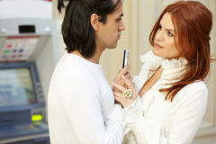 Dark-haired man with credit card in hand and red-haired woman Stock Images