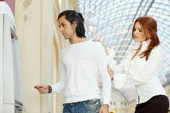 Dark-haired man with credit card and red-haired woman stand Stock Photos