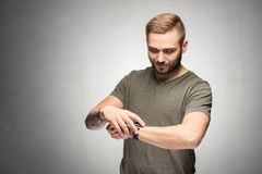 Man checking time on his watch. Portrait. Dark-haired man looking down at a watch on his hand, checking time. Chill, relaxed expression Stock Photos