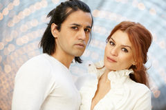 Dark-haired man and red-haired woman stand side by side Royalty Free Stock Photos