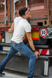 Dark-haired man trying to lift heavy vehicle Royalty Free Stock Images