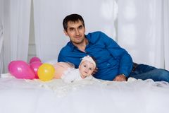 A dark-haired man posing lying on the bed with his little daughter who smiles and looks at everything on the sides. He. A dark-haired men posing lying on the bed royalty free stock photo