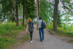Dark-haired middle-aged man and red-haired young lady walk along. Forest road. Tourists on the beautiful landscape background. Monrepos Park, Vyborg, Russia royalty free stock image