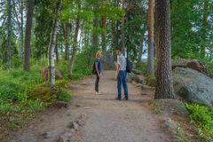 Dark-haired middle-aged man and red-haired young lady walk along. Forest road. Tourists on the beautiful landscape background. Monrepos Park, Vyborg, Russia stock images