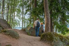 Dark-haired middle-aged man and red-haired young lady walk along. Dark-haired middle-aged men and red-haired young lady walk along forest road. Tourists on the royalty free stock photography
