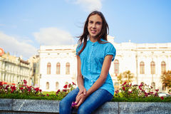 Dark-haired pretty teenage girl sitting on the street flowerbed Stock Image