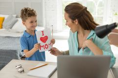 Dark-haired remote worker on maternity leave spending time with son. Maternity leave. Beautiful dark-haired remote worker on maternity leave feeling very happy stock image