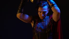 The dark haired Roman gladiator with tattoo, his leather armor and raincoat takes off his heavy helmet and stares at the. The dark-haired Roman warrior with stock video
