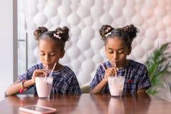 Dark-haired sisters wearing bright hair slides enjoying their milkshakes. Hair slides. Dark-haired cute fashionable sisters wearing bright hair slides enjoying royalty free stock photo
