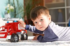 Dark haired small kid plays with toy car in bedroom, looks directly in camera, being glad to recieve new toy from parents, lies on. Floor. Little male kid with stock photography