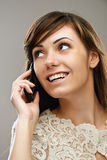 Dark-haired smiling woman talking on phone Royalty Free Stock Photo